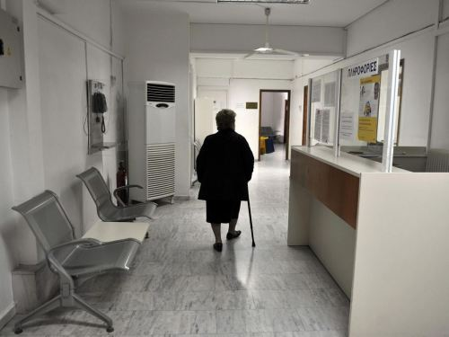 A woman walks a closed branch Greek state health fund EOPYY in an Athens suburb