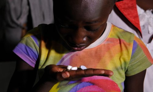A young girl living with Aids takes her drugs at her home in Ndiwa, western Kenya. Photograph: Simon Maina/AFP/Getty Images
