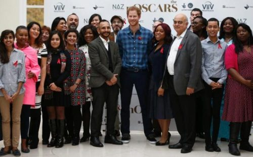 Prince Harry poses with staff and donors of Naz CREDIT: PETER NICHOLLS/REUTERS