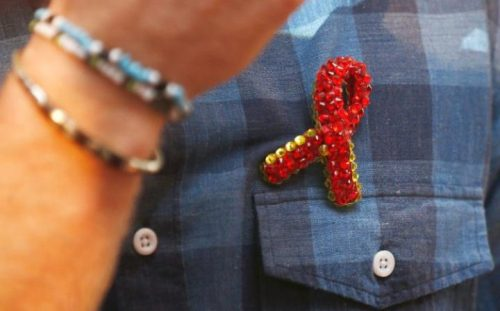 The Prince was given a brooch made of glass beads to represent the red ribbon worn to show support for those with HIV CREDIT: PETER NICHOLLS/REUTERS